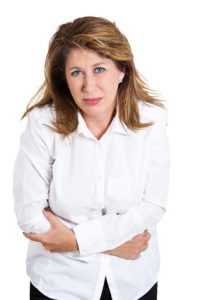 Closeup portrait, mature, stressed woman, placing hands on stomach having bad aches, pains, isolated white background. Food poisoning influenza cramps. Negative emotion, facial expression, reaction